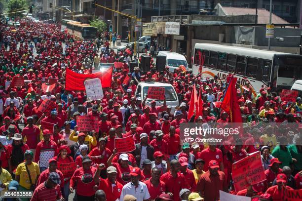 Members of South Africa's main labour union federation COSATU carry placards and flags during a demonstration calling for the removal of South...