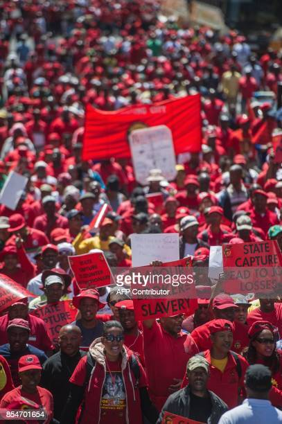 Members of South Africa's main labour union federation COSATU carry placards during a demonstration calling for the removal of South Africa's...