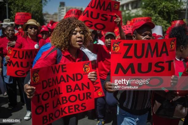 Members of South Africa's main labour union federation COSATU wave placards during a demonstration calling for the removal of South Africa's...