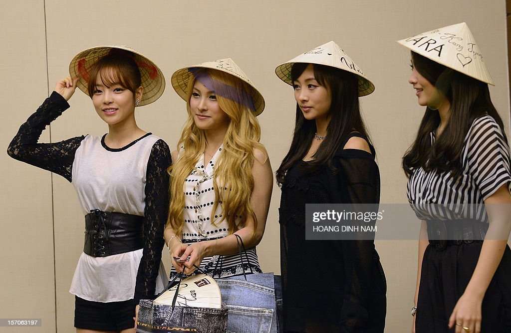 Members of South Korean pop band Kara wear conical hats offered by their local Vietnamese fans during a press conference held in Hanoi on November 28, 2012. Seventeen SKorean pop bands will perform in the Vietnamese capital on November 29 to mark the 20th anniversary of the establishment of diplomatic ties between Vietnam and South Korea. AFP PHOTO/HOANG DINH Nam