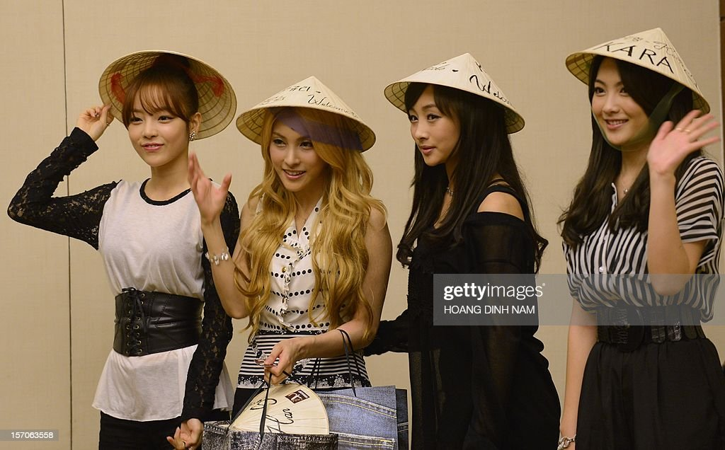 Members of South Korean pop band Kara wear conical hats offered by their local Vietnamese fans as they attend a press conference held in Hanoi on November 28, 2012. Seventeen SKorean pop bands will perform in the Vietnamese capital on November 29 to mark the 20th anniversary of the establishment of diplomatic ties between Vietnam and South Korea. AFP PHOTO/HOANG DINH Nam