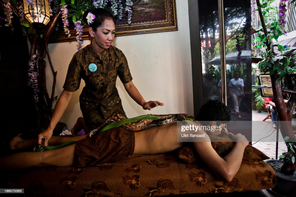 Members of staff demonstrate a form of massage using pythons at Bali Heritage Reflexology and Spa on October 27, 2013 in Jakarta, Indonesia. The snake spa offers a unique massage treatment which involves having several pythons placed on the customers body. The movement of the snakes and the adrenaline triggered by fear is said to have a positive impact on the customers metabolism.