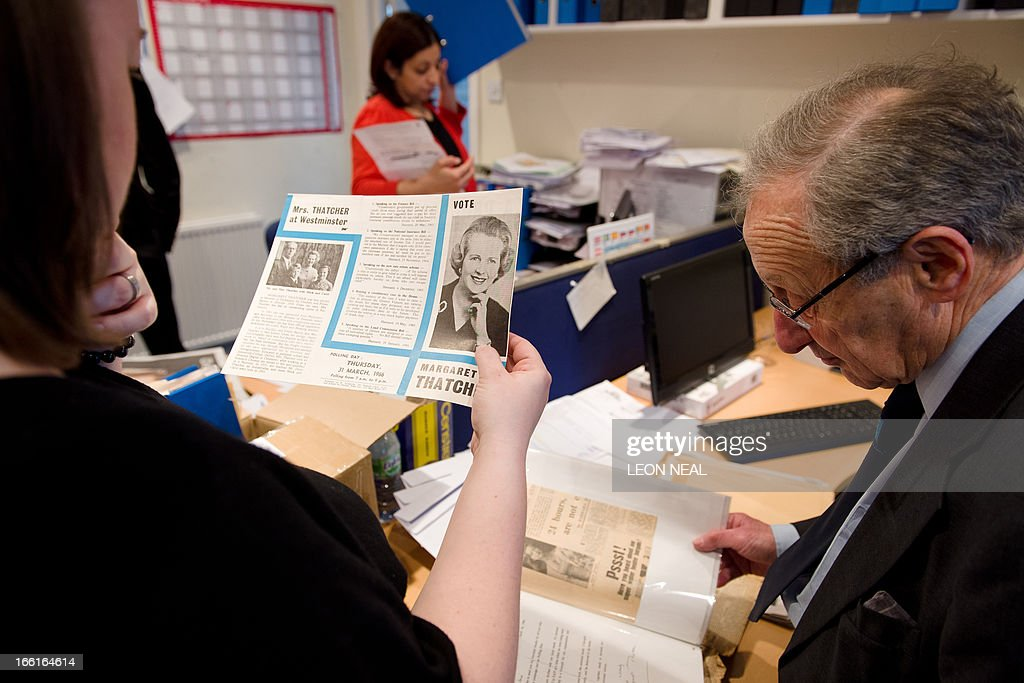 Members of staff look through a box of old newspaper cuttings and campaign memorabilia from the local election campaigns of former British Prime Minister Margaret Thatcher at the Conservative Party headquarters in Finchley, north London on April 9, 2013. Thatcher was elected MP for Finchley in 1959 and her funeral will take place on April 17, current premier David Cameron's Downing Street office said Tuesday. AFP PHOTO/Leon Neal