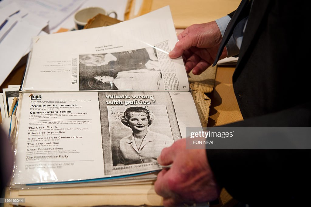 Members of staff look through old newspaper cuttings and campaign memorabilia from the local election campaigns of former British Prime Minister Margaret Thatcher at the Conservative Party headquarters in Finchley, north London on April 9, 2013. Thatcher was elected MP for Finchley in 1959 and her funeral will take place on April 17, current premier David Cameron's Downing Street office said Tuesday. AFP PHOTO/Leon Neal