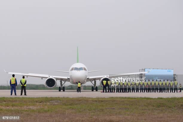 Members of staff stand in front of China's homegrown C919 passenger jet after its maiden flight at Pudong International Airport in Shanghai on May 5...