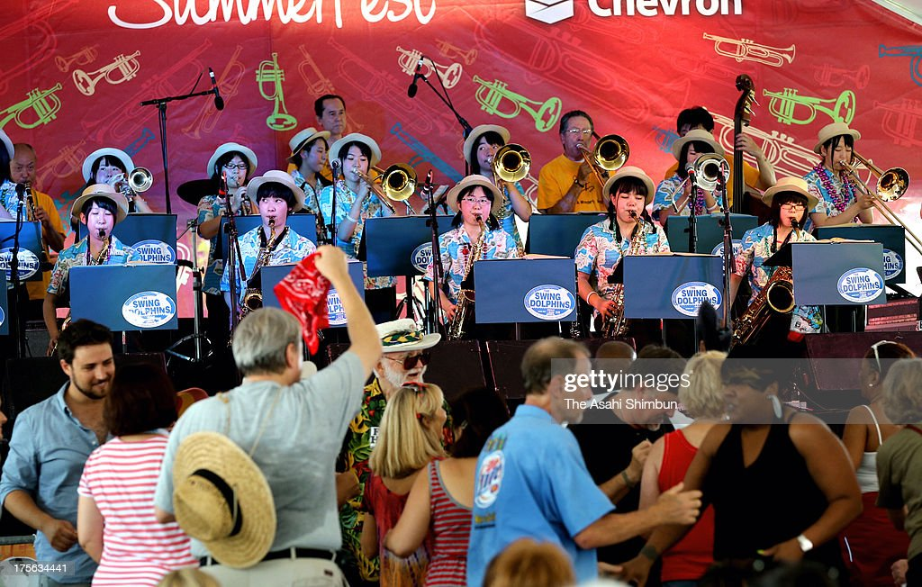 Members of 'Swing Dolphines', junior highschool jazz band performs while audience dance during the Satchmo Summerfest on August 3, 2013 in New Orleans, Louisiana. The band perform to appreciation of the support of New Orlean, after they lost their music instruments by the Magnitude 9.0 earthwquake and subsequent tsunami two years ago, could resume their activity thanks to the donations from the clubs of the city.