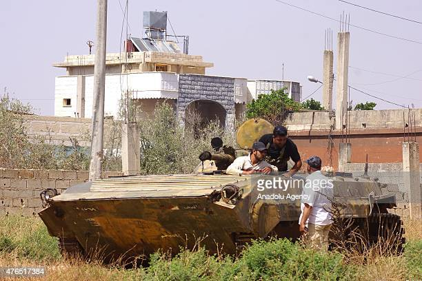 Members of Syrian opposition forces are seen on a tank after they seized the control of 52nd Brigade one of the biggest brigades of Assad Regime in...