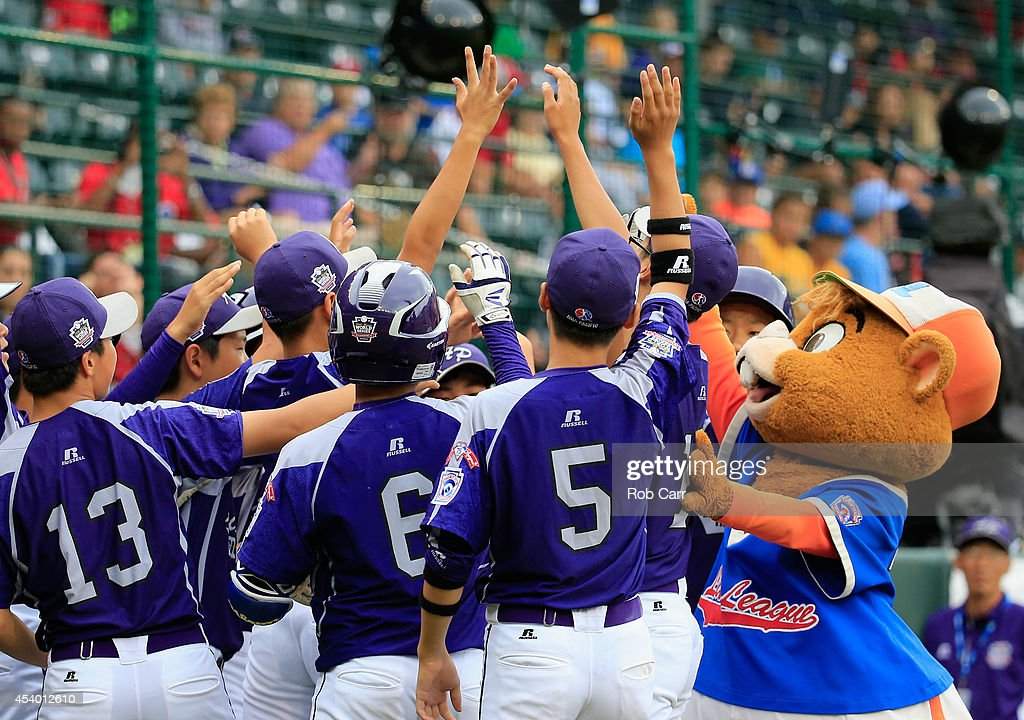 Members of Team Asia-Pacific dance with mascot Dugout before the start of their game against Team Japan during the International Championship game of the Little League World Series at Lamade Stadium on August 23, 2014 in South Williamsport, Pennsylvania.