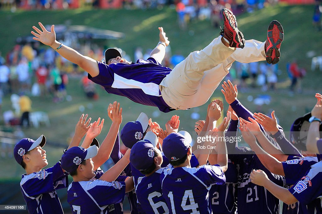 Members of Team Asia-Pacific (L) throw an assistant coach in the air following their 8-4 win over the Great Lakes Team from Chicago, Illinois to win the Little League World Series Championship game at Lamade Stadium on August 24, 2014 in South Williamsport, Pennsylvania.