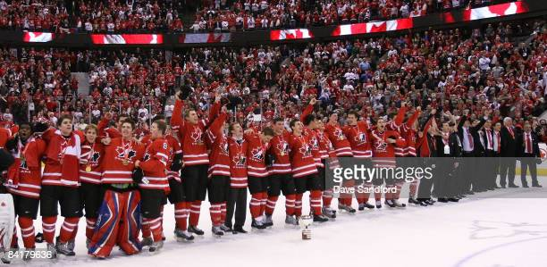 Members of Team Canada stand arm in arm as they sing the Canadian National Anthem after defeating Team Sweden during the 2009 IIHF World Junior...