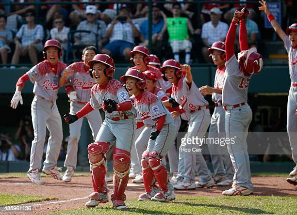 Members of team Japan celebrate while waiting for Masafuji Nishijima to score after hitting a three RBI home run against the MidAtlantic team from...