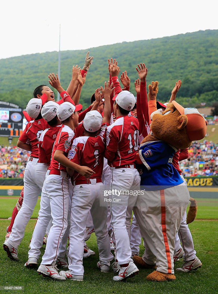 Members of Team Japan dance with mascot Dugout before the start of their game against Team Asia-Pacific during the International Championship game of the Little League World Series at Lamade Stadium on August 23, 2014 in South Williamsport, Pennsylvania.