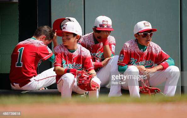 Members of team Mexico wait to take the field against team Japan during the seventh inning of International Championship game of the Little League...