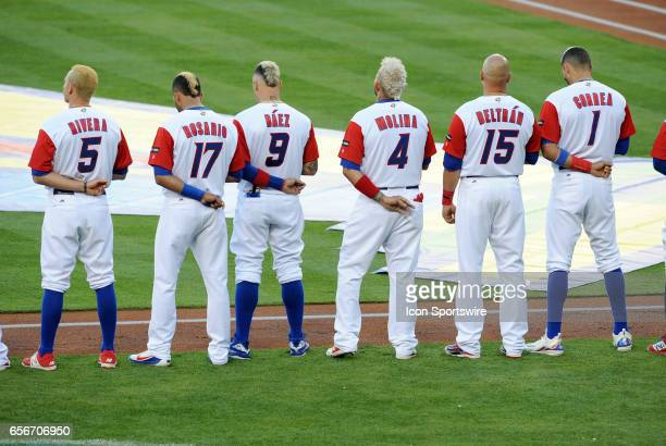 Members of team Puerto Rico with bleached blonde hair line up for the national anthem before the start of the World Baseball Classic finals game...