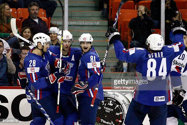 Members of Team Slovenia congratulate Marjan Manfreda of Slovenia on his second period goal during the game against Slovakia at the IIHF World Ice...