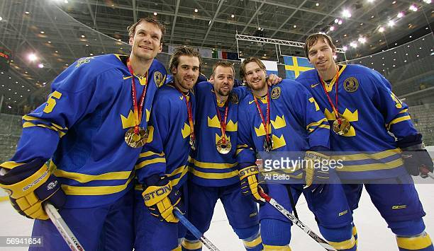 Members of team Sweden celebrate with their gold medals after defeating Finland 32 to win the gold medal in the final of the men's ice hockey match...