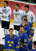 Members of team Sweden wait to receive their gold medals in front of team Finland waiting to receive their silver medals after Sweden defeated...