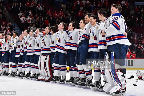 Members of Team United States lock arms and sing the US national anthem during the 2017 IIHF World Junior Championship gold medal game against Team...
