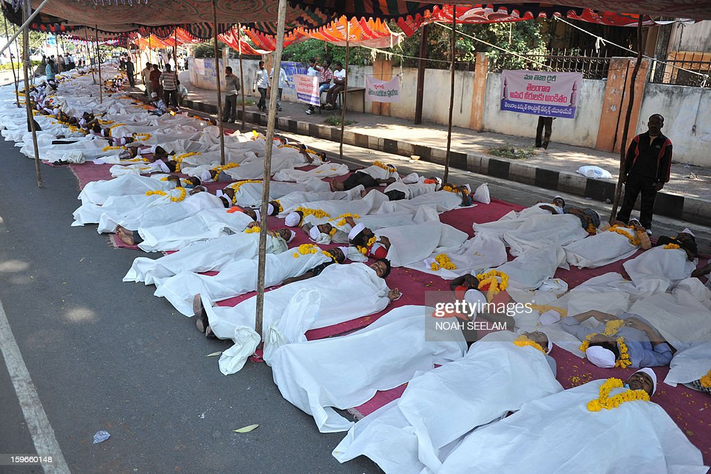 Members of Telangana Joint Action Committe (TJAC) lie on a road during a silent protest demanding the separate state of Telangana in Hyderabad on January 18, 2013. The TJAC demanded the UPA governement to announce statehood for Telangana in the southern Indian state of Andhra Pradesh. AFP PHOTO / Noah SEELAM