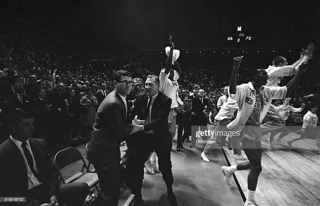 Members of Texas Western rush onto the court as the final gun sounded giving them a 72-65 win over the Kentucky Wildcats and the NCAA basketball championship in the Cole Field House 3/19. The Texas Western coach Don Haskins, 2nd from left, and his assistant, Henry (Moe) Iba, congratulate each other.