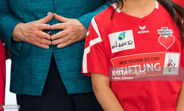 Members of the 1 FC Koeln Foundation and members of the initiative 'Wir zusammen' wear a shirt with special print on it next to German Chancellor...