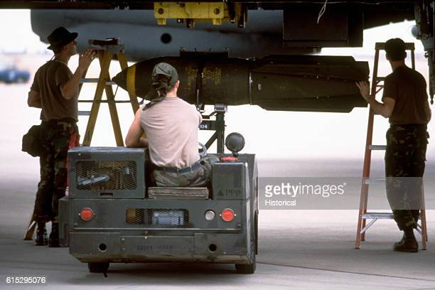 Members of the 1708th Munitions Maintenance Squadron use an MJ1 bomb loader to load M117 750pound bombs onto a B52G Stratofortress bomber aircraft...