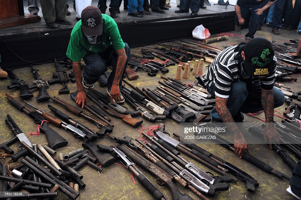 Members of the '18 street' gang rifles during an event to hand in weapons in Apopa, 14 Km north of San Salvador, El Salvador on March 9, 2013. Gang leaders surrendered about 267 weapons as part of the truce process between gangs in El Salvador. AFP PHOTO/ Jose CABEZAS