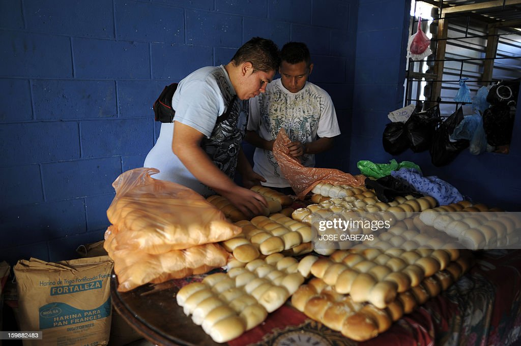 Members of the 18th street gang put bread into bags at a bakery operated by them as a part of a rehabilitation program in San Bartolo neigbourhood, in Ilopango, a suburb of San Salvador on January 21, 2012. Gang leaders started the second phase of the gang truce to reduce crime in El Salvador. AFP PHOTO/ Jose CABEZAS
