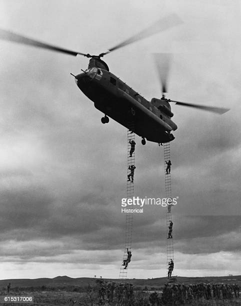 Members of the 1st Cavalry Division climb ladders hanging from a Boeing CH47A Chinook helicopter near Pleiku Vietnam | Location Near Pleiku Vietnam
