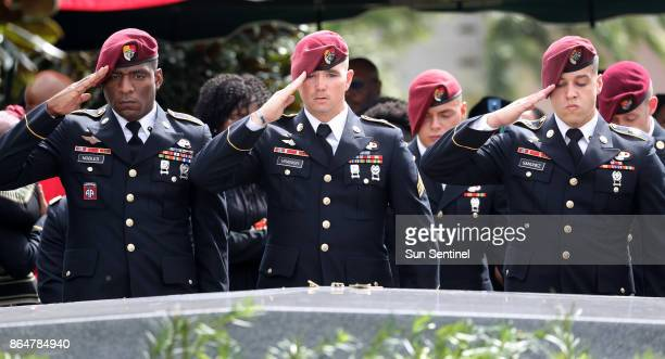 Members of the 3rd Special Forces Group Airborne 2nd Battalion leave pins and salute the casket after the burial of Army Sgt La David Johnson at Fred...