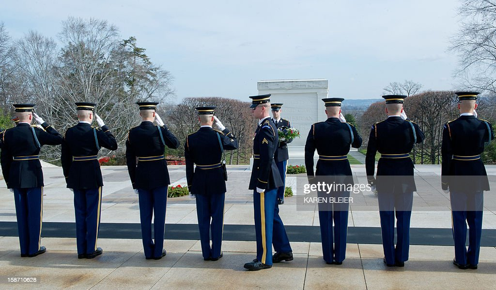 Members of the 3rd United States Infantry Regiment, 'The Old Guard,' Tomb Guards, salute during a wreath laying ceremony at the Tomb of the Unknowns, December 25, 2012 in Arlington National Cemetery in Virginia. AFP PHOTO /Karen BLEIER