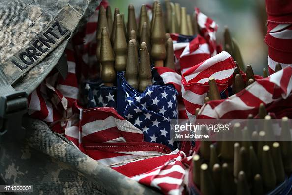 Members of the 3rd US Infantry Regiment load American flags into their backpacks before placing them at the graves of US soldiers buried at Arlington...