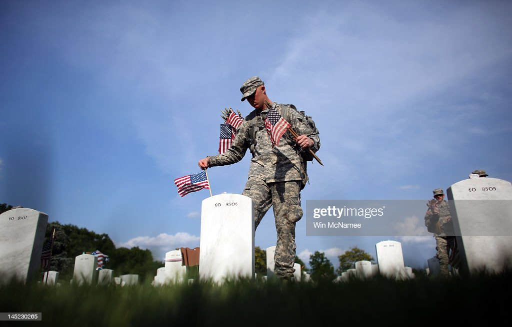 Members of the 3rd U.S. Infantry Regiment place American flags at the graves of U.S. soldiers buried in Section 60 at Arlington National Cemetery in preparation for Memorial Day May 24, 2012 in Arlington, Virginia. 'Flags-In' has become an annual ceremony since the 3rd U.S. Infantry Regiment (The Old Guard) was designated to be an Army's official ceremonial unit in 1948. Every available soldier in the 3rd U.S. Infantry Regiment participates in these events.