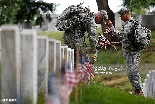 Members of the 3rd US Infantry Regiment place American flags at the graves of US soldiers buried at Arlington National Cemetery in preparation for...