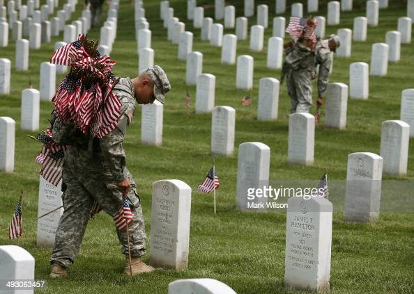 Members of the 3rd US Infantry Regiment 'The Old Guard' place flags at grave sites during the 'FlagsIn' ceremony May 24 2014 at Arlington National...