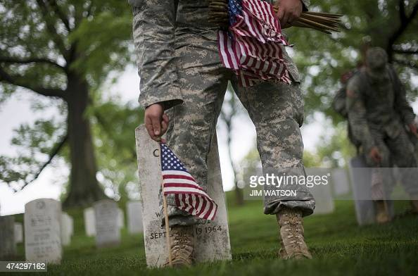 Members of the 3rd US Infinity Regiment place American flags at the foot of graves in Arlington National Cemetery in Arlington Virginia on May 21...