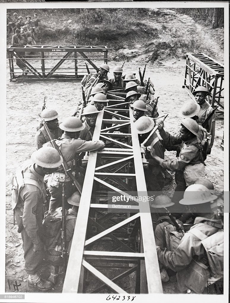 Members of the 41st Engineers labor to swing onto a place a section of an H19 bridge during maneuvers