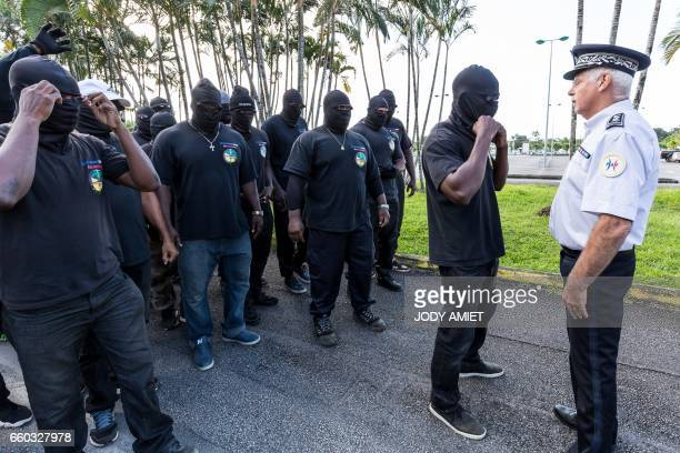 TOPSHOT Members of The 500 Brothers face off with police during a protest in support of the general strike on March 29 2017 in Cayenne French Guiana...