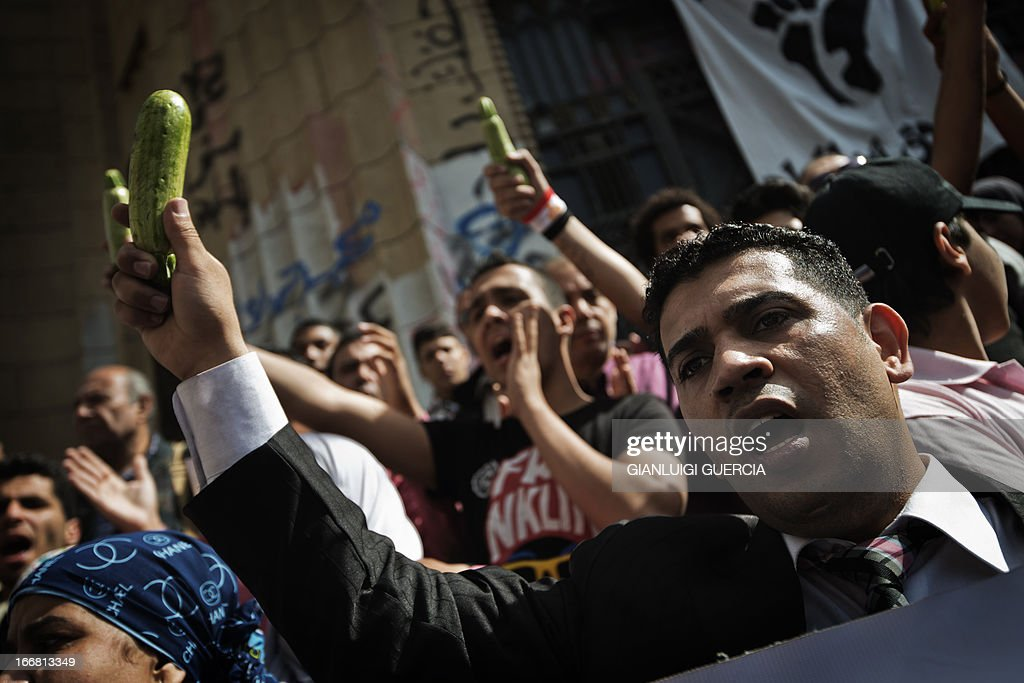 Members of the 6th of April movement and relatives of people killed in the 2011 Egyptian revolution hold courgettes, which represent corruption and nepotism in Egyptian culture, as they shout anti-government slogans and demand for the release of political prisoners during a demonstration outside the Egyptian High Court in Cairo on April 17, 2013. A retrial of former Egyptian president Hosni Mubarak over his role in the deaths of protesters in 2011 is to open on May 11, judicial sources told AFP. AFP PHOTO/GIANLUIGI GUERCIA
