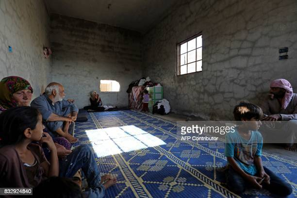 TOPSHOT Members of the Abu Ghanem family sit inside a home where they are taking shelter in Raqa's western alSabahiya district on August 14 2017 The...