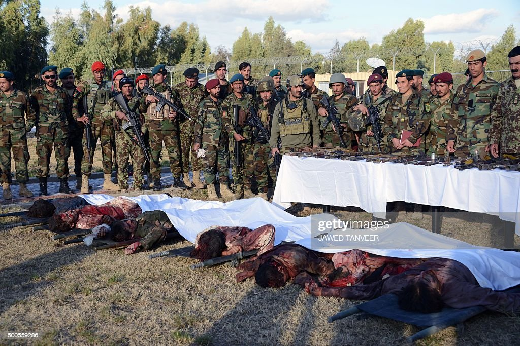 TOPSHOT Members of the Afghan military stand near bodies of Taliban militants wearing Afghan army uniforms who were killed during clashes against...