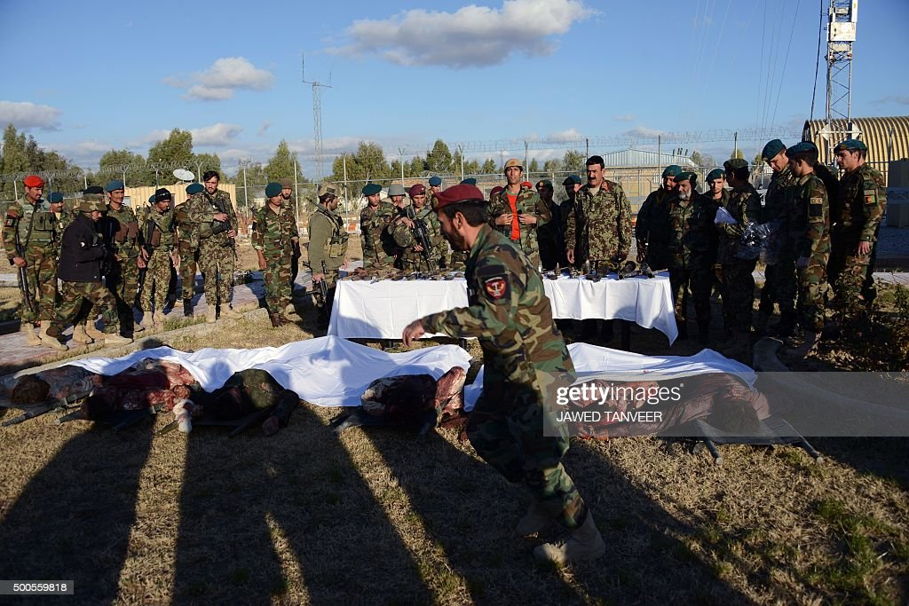 Members of the Afghan military stand near bodies of Taliban militants wearing Afghan army uniforms who were killed during clashes against security...
