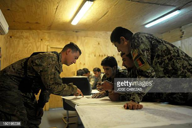 Members of the Afghan National Army are helped by a US soldier as they participate in a map reading training session at Narizah base in Narizah Khost...