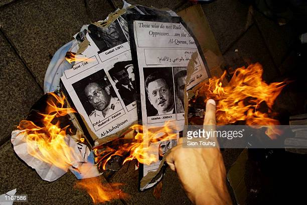 Members of the Al Muhajiroun Islamic fundamentalist group burn placards depicting leaders of Islamic states as traitors of Islam October 12 2001 at a...