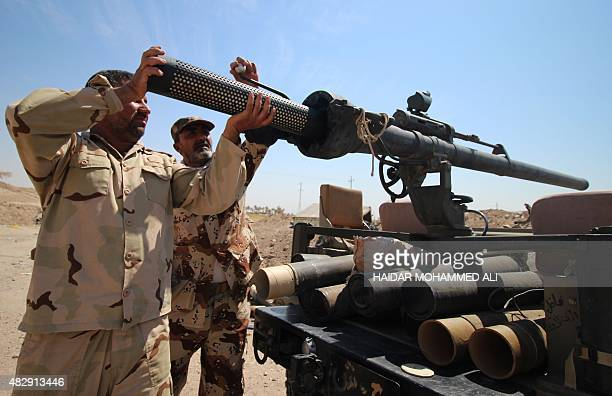 Members of the allied Iraqi forces consisting of the Iraqi army and fighters from the Popular Mobilisation units load heavy artillery on the front...