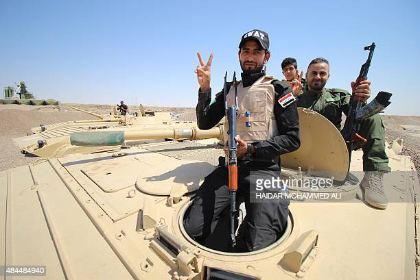 Members of the allied Iraqi forces consisting of the Iraqi army and fighters from the Popular Mobilisation units pose for a photo as they sit on a...