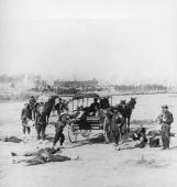 Members of the Ambulance Corps collect the wounded from the battlefield on stretchers and load them into a horsedrawn wagon during the American Civil...