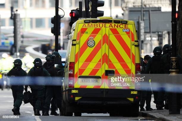 Members of the Ambulance service wearing protective clothing arrive on the scene outisde the Houses of Parliament in central London on March 22...