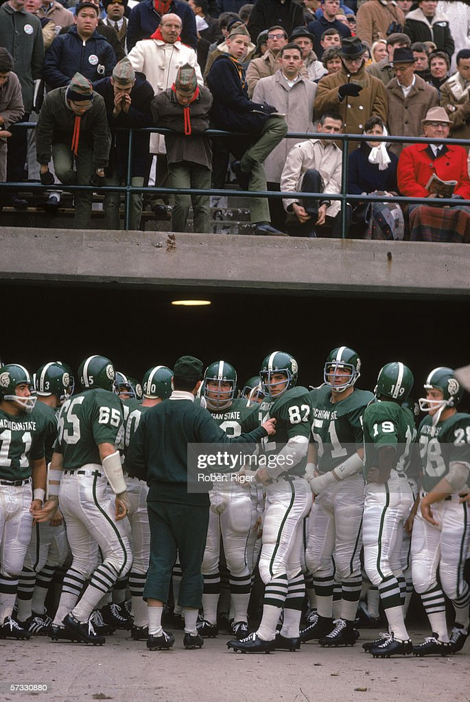 Members of the American college football team from Michigan State gather around a coach on the sidelines during a game against the Notre Dame...