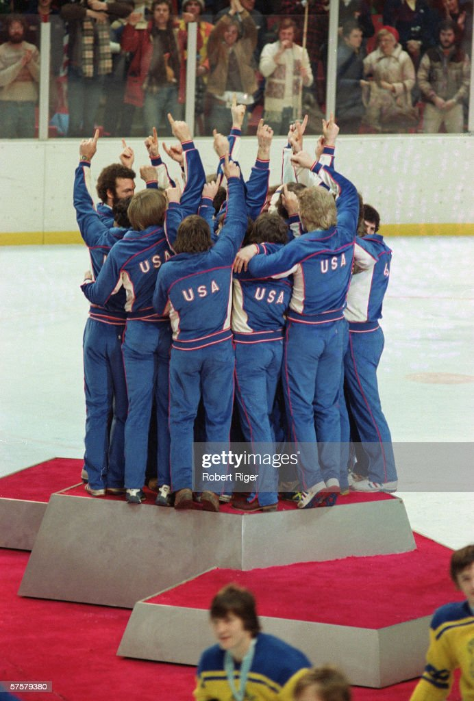 Members of the American Men's Olympic ice hockey team make the 'We're number one' gesture as they celebrate on the medal podium after receiving their gold medals, Lake Placid, New York, February 24, 1980. Team USA won the gold after defeating Finland but are best remembered for their victory over the Soviet team two days earlier, an event known as the 'Miracle on Ice.' Bronze-winning Swedes are seen at bottom right.